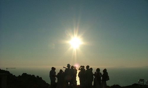 A group of people beneath the sun.